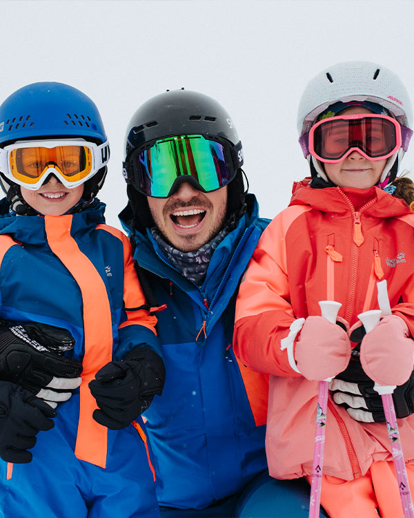 Man with children in skiwear and wearing helmets